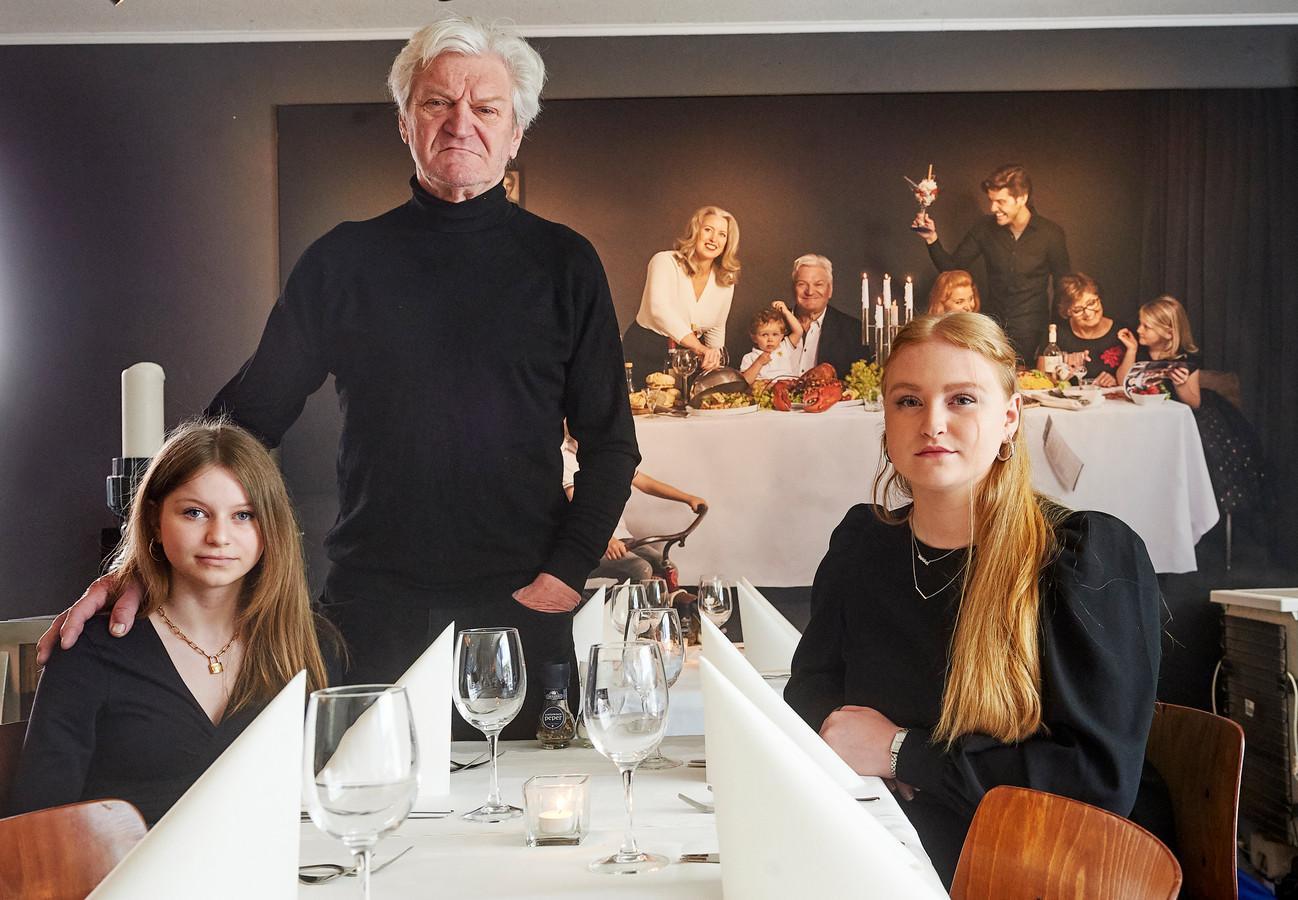 Rosa (13) en Anna (19) samen met vader Bo de Marco in het restaurant van hun moeder aan de Houtstraat in Oss. Op de achtergrond een grote foto van de hele familie, met moeder Hanneke in haar natuurlijke rol als gastvrouw.