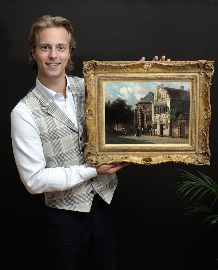 EDE - Kunsthandelaar Kas Buunk van Galerie Simonis en Buunk te Ede, 13 sep 2018 met een schilderij van een Woerdens stadsgezicht. Woerden, stadsgezicht, Buunk