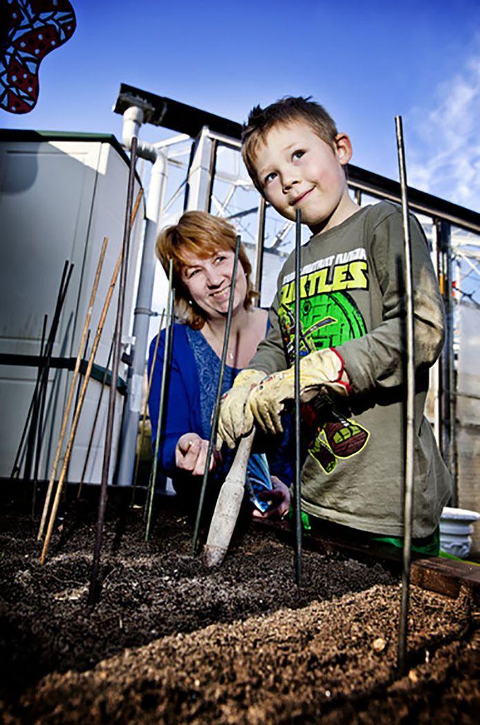 Samen met zijn moeder Patricia zaait Michael de tuinbonen in.