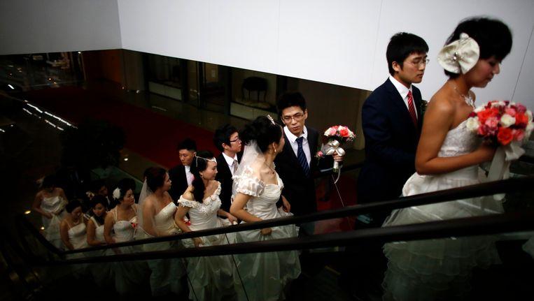 Chinese koppels staan in de rij om in het huwelijksbootje te stappen. Beeld Reuters