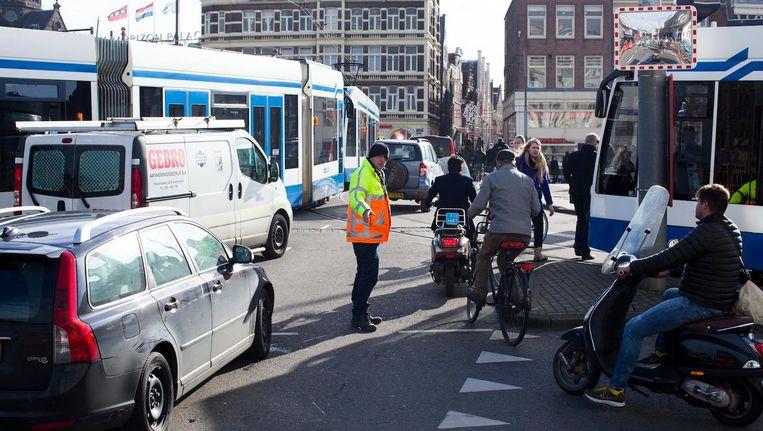 Een verkeersregelaar probeert de doorstroming op gang te houden tijdens de drukte op de Prins Hendrikkadebij het Centraal Station. Beeld Holandse Hoogte