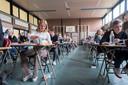 In de gymzaal van de school - zeil op de vloer, rijen bruine tafels - mag je zelf je plek kiezen. Let op het bakje snoeptomaatjes bij de tafelpoot.
