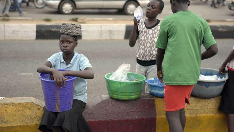 Nigeriaanse kinderen proberen hun waar te verkopen langs de kant van de weg Beeld afp