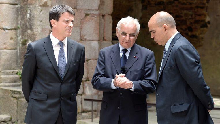De Franse premier Manuel Valls (links) en staatssecretaris voor Veteranen en Defensie Kader Arif (rechts) luisteren naar een van de enige overlevenden van het bloedbad, Robert Hebras (86).