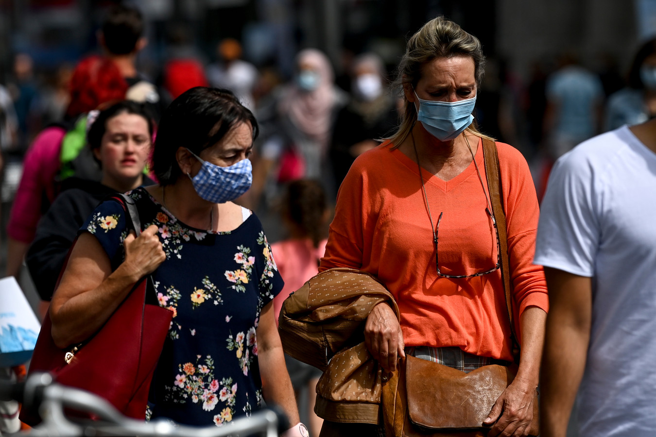 Inwoners van Antwerpen dragen mondkapjes tijdens het winkelen.