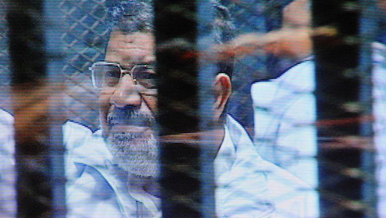 Mohammed Morsi (rechts) staat in een glazen kooi in de rechtbank in Caïro. Beeld ap