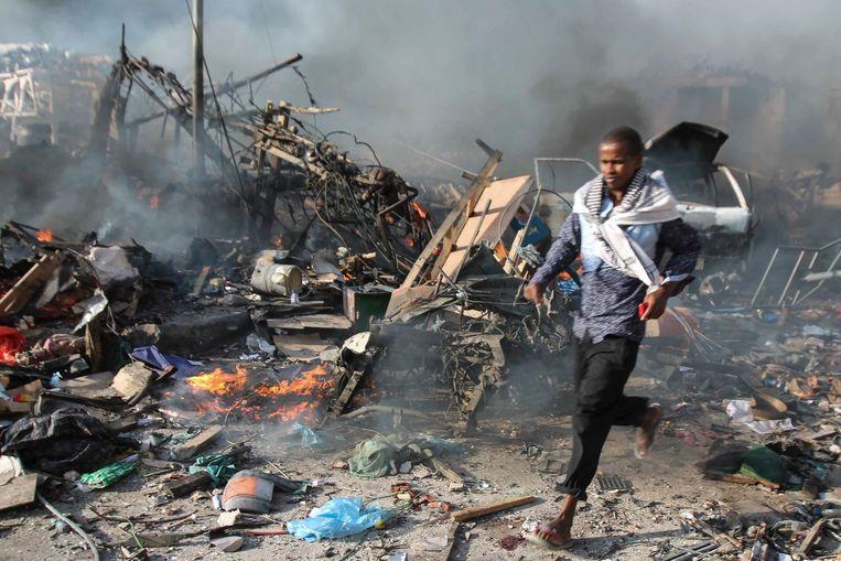 Een man loopt door het puin na een bomaanslag met een vrachtwagen voor het Safari Hotel in Mogadishu, op 14 oktober jongstleden.
