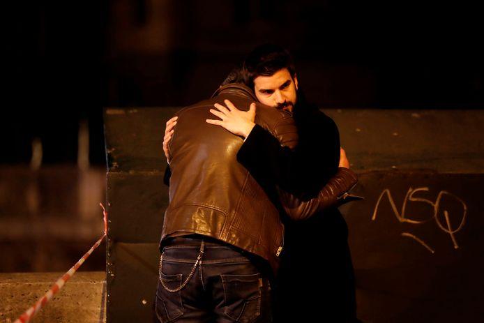 Twee mannen zoeken troost bij elkaar, een lint scheidt hen van de plek waar de bekendste kerk van Frankrijk in vlammen opgaat.