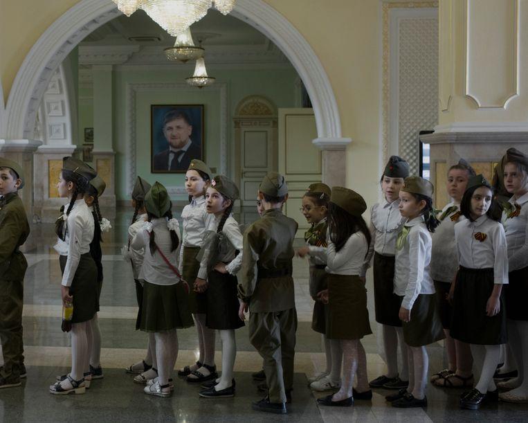 Kinderen tijdens een excursie in het Akhmad Kadyrov Museum, waar onder meer een portret hangt van Ramzan Kadyrov. Beeld Emile Ducke