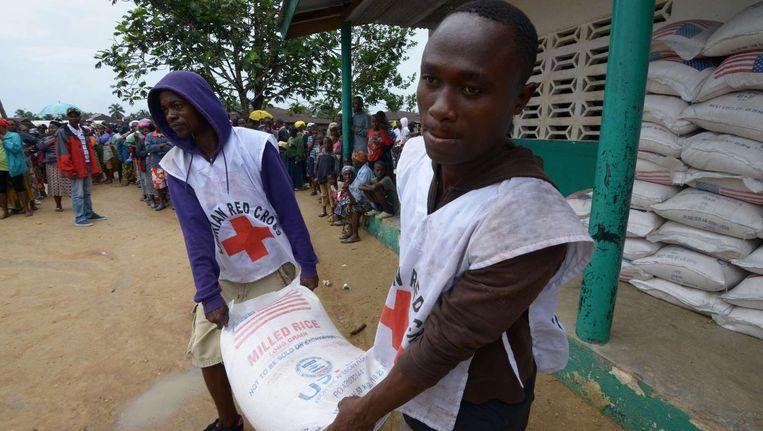 Medewerkers van het Liberische Rode Kruis dragen zakken met rijst voor de wijk in Monrovia die is afgesloten wegens de ziekte ebola. Beeld afp