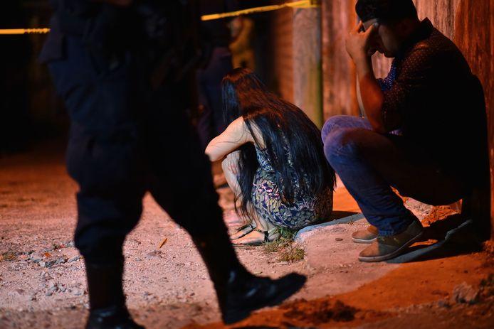 Familieleden zitten aangeslagen buiten de bar waar schutters dertien mensen om het leven brachten.