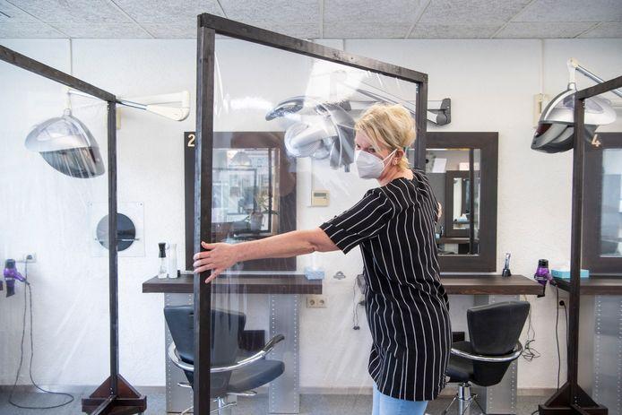 Naast een aparte eenpersoonsruimte heeft Geke Herssevoort schermen die ze tussen klanten zet. En de kapsters dagen mondkapjes.