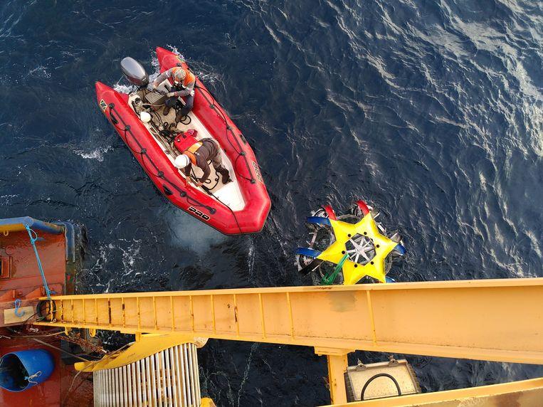 Onderzoekers laten een drijver met detectorbollen in de Middellandse Zee zakken. De drijver en de detectoren maken deel uit van de KM3NeT, waarmee naar neutrino's wordt gespeurd. Beeld Ernst-Jan Buis