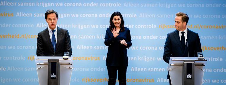 Premier Mark Rutte, Minister Hugo de Jonge, en in het midden gebarentolk Irma Sluis tijdens de persconferentie van dinsdagavond.  Beeld ANP