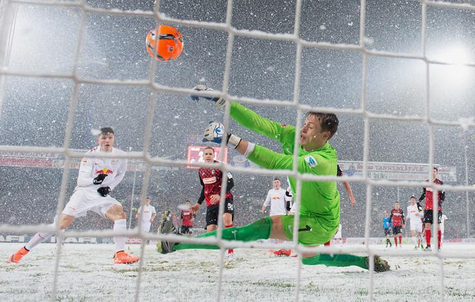 Sneeuwbalgevecht! Doelman Alexander Schwolow van Freiburg redt op een inzet van dichtbij tegen Red Bull Leipzig in maart van dit jaar.