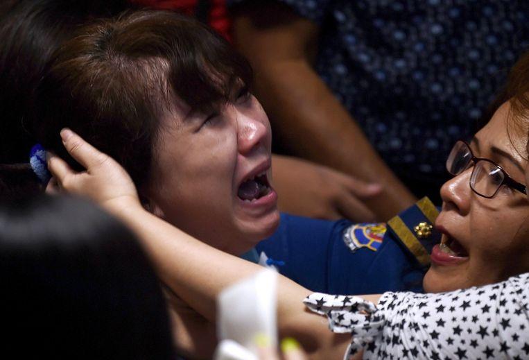 Familileden reageren op beelden van een half ontbloot lichaam drijvend in de Javazee, die worden getoond in het crisiscentrum op de luchthaven van Surabaya. Beeld afp