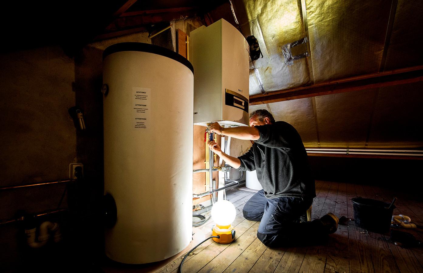 Een installateur is bezig met het installeren van een warmtepomp bij een verwarmingsketel, als onderdeel van een project om een jaren-60 woning energiezuinig te maken. Foto ter illustratie.