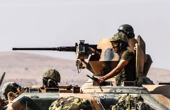 Turkse militairen rijden in een tank Syrië binnen.