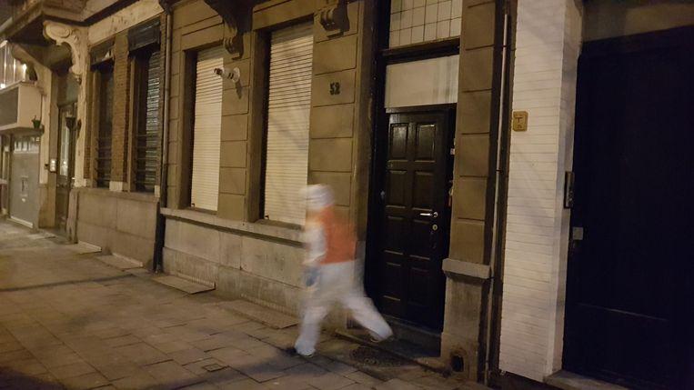 Een laborant van de politie verlaat de woning in de Van Stralenstraat.