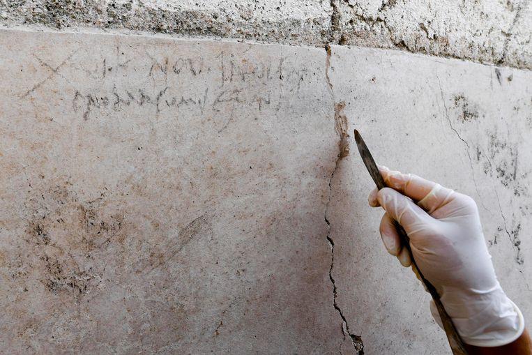 Een archeologe onderzoekt de inscriptie.