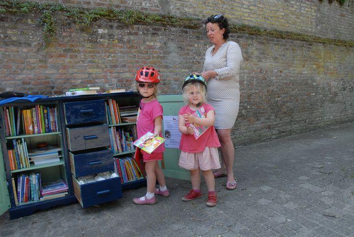 Amelie(5) en Charlotte(3) Costa hebben een (gratis) boek te pakken bij het kersverse Kinderzwerfboekenstation in het Tilmanshofje. Ambassadeur Elke de Quay legt aan alle kinderen uit hoe het werkt.
