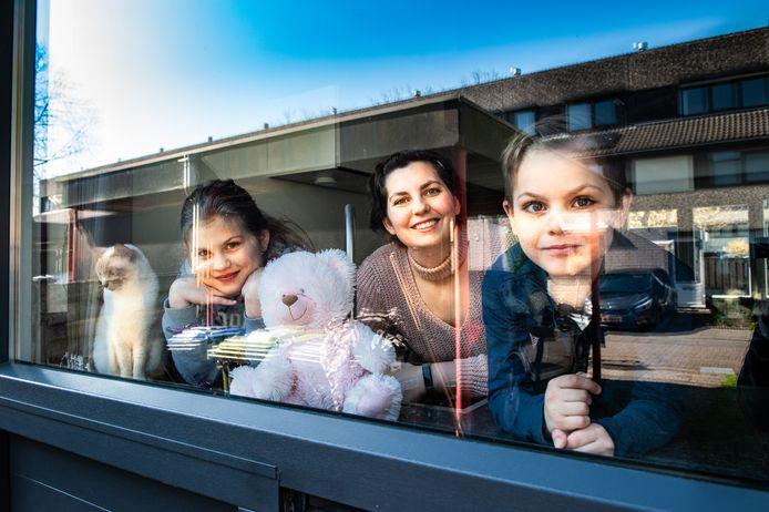 Chantal Schröder en haar kinderen Cloë en Lucas hebben beer Lina in het keukenraam gezet in de wijk Bloemendaal voor de berenjacht. (Naam poes onbekend).