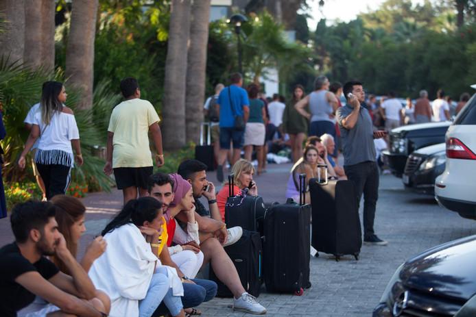 Hotelgasten wachten op de stoep op wat komen gaat, nadat het pand werd ontruimd.