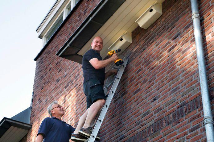 Johan Sterk en Fulco van Lieven (r) hangen in augustus 2015 een nestkast op bij een woning aan de Dalem Donk.