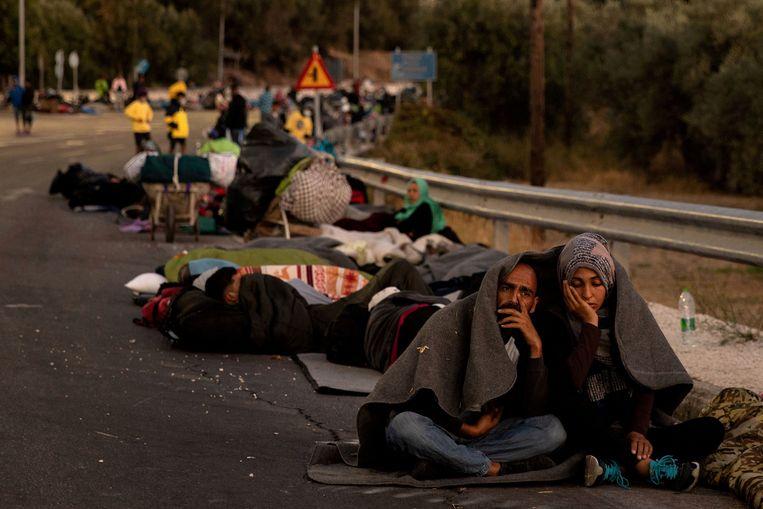 Migranten langs de kant van de weg na de brand in kamp Moria. Beeld REUTERS