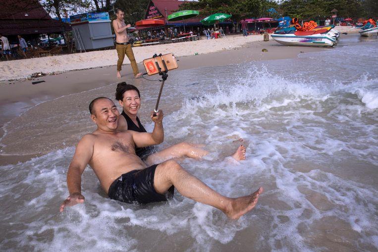 Chinese toeristen vermaken zich op het strand van Sihanoukville.  Beeld Getty Images