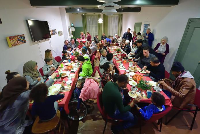 Statushouders ontmoeten elkaar en genieten van een eenvoudige kerstmaaltijd, waar ondertussen hoofdzakelijk Nederlands wordt gesproken.