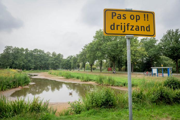 Met borden wordt gewaarschuwd voor drijfzand in de drooggevallen vijver langs de Haaksbergerstraat in Enschede.