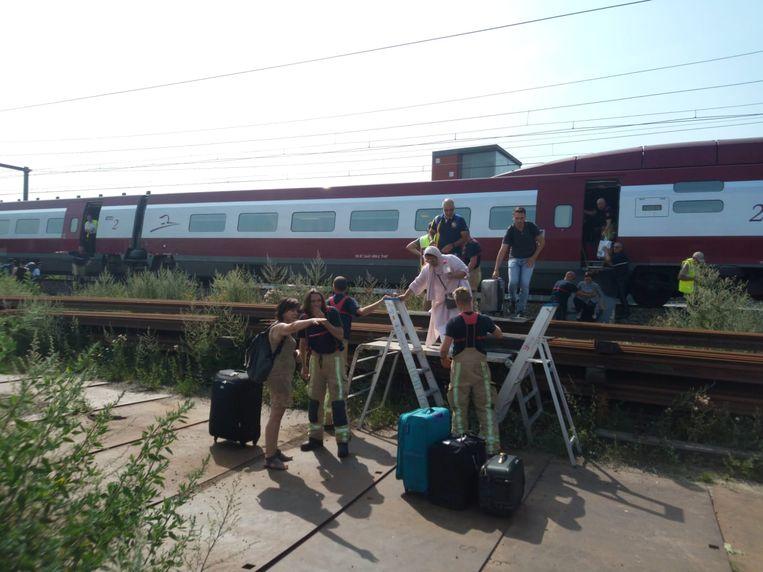 Brandweerlui helpen de inzittenden van een stilgevallen Thalys-trein in Mechelen met de evacuatie.