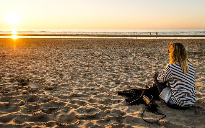 Een meisje ziet de zon ondergaan op het strand bij Bloemendaal