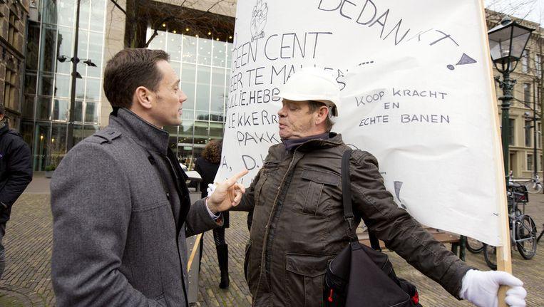VVD-Kamerlid Sjoerd Potters (L) in december 2013 in gesprek met een demonstrant op het Plein in Den Haag Beeld anp