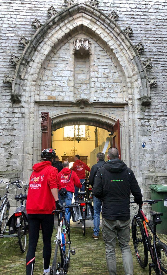 De Vuelta 2020 voert dwars door de Grote Kerk van Breda. De renners lopen met de fiets aan de hand door het monumentale pand.