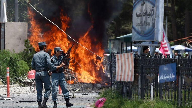 Politieagenten onderzoeken de plek waar een auto vol explosieven op een ingang van het vliegveld reed. Beeld afp