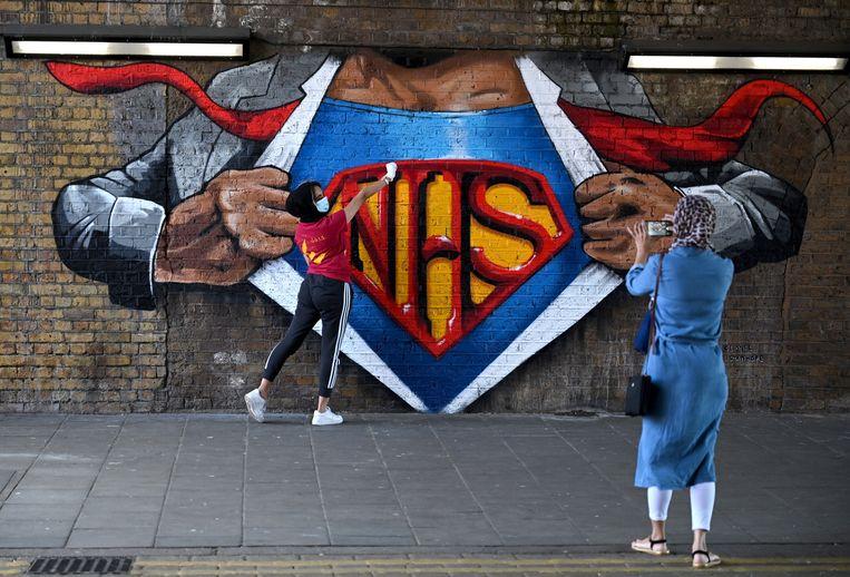 Een vrouw poseert voor een muurschildering, dat de nationale gezondheidsdienst NHS eert.  Beeld EPA