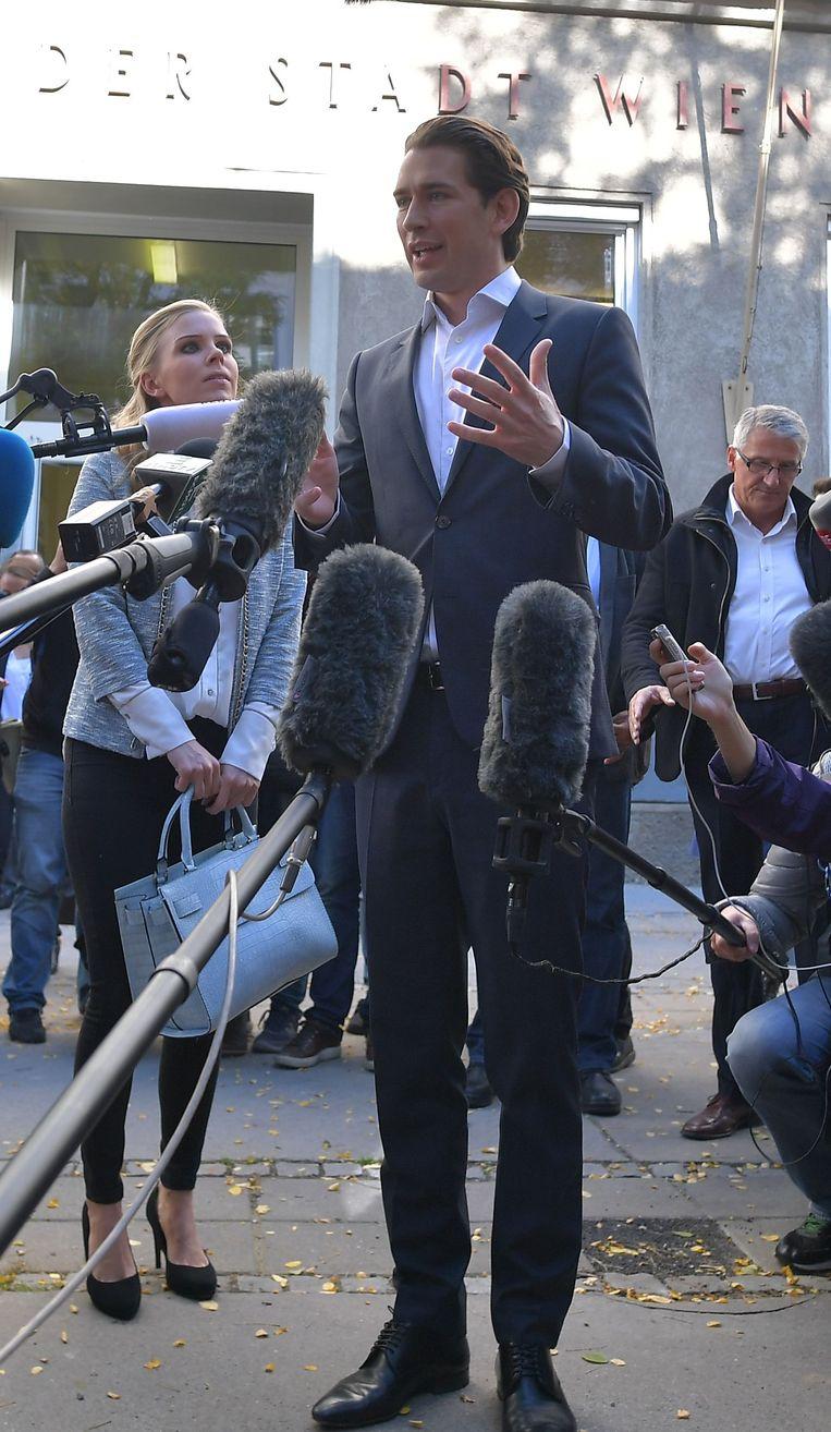 Kurz spreekt de pers toe aan het stembureau. Zijn vriendin Susanne (30) - met wie hij al 12 jaar samen is - hangt aan zijn lippen.