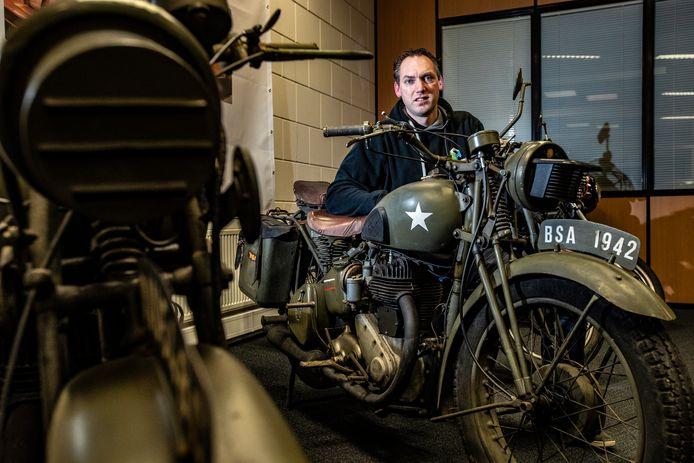 Dirk Berends poseert bij één van de klassieke motoren die uit de collectie van zijn overleden opa Henk Koldenhof komt en geveild wordt.