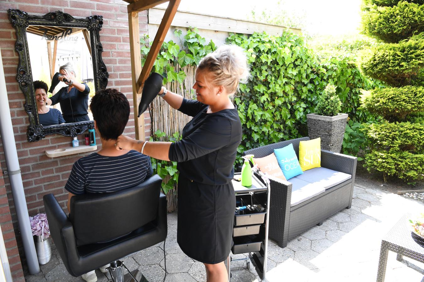 TILBURG,  Foto PixProfs/Jan Stads Kapsalon Trendline heeft de halve kapperszaak naar de tuin verplaatst. De buitenkapper dus. Eigenaresse Renée van Gils föhnt haar klant Corona van Riel