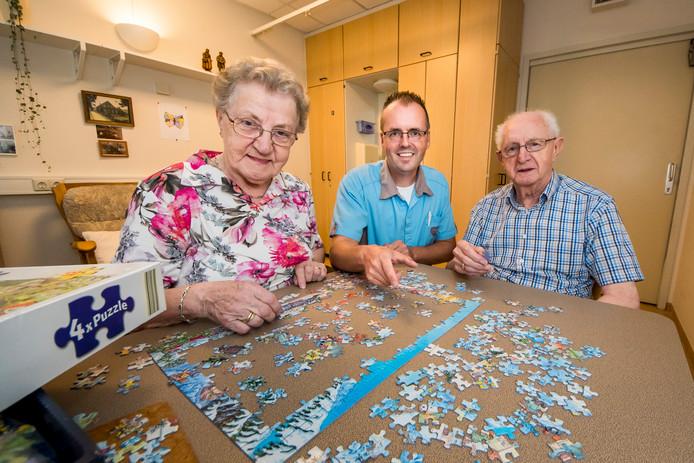 Berty Lensink bezoekt haar demente man Wim elke dag in verpleeghuis Herinckhave, waar ze samen puzzelen. In het midden verpleegkundige Mark Boonstra.