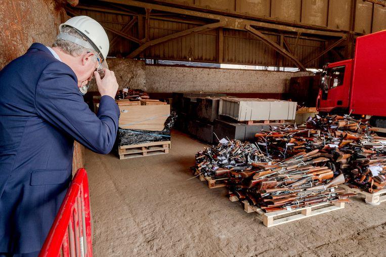 Minister van Binnenlandse Zaken en Veiligheid Pieter De Crem bekijkt de stapels wapens.