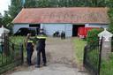 Politieagenten onderzoeken een schuur op een boerenerf