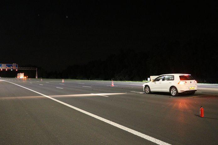 De witte personenauto die achterop de vrachtwagen reed die verder langs de Lege A2 bij Maarssen geparkeerd staat.