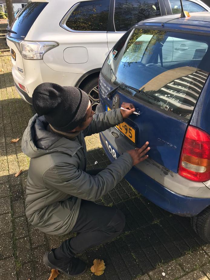 Rapper Typhoon schrijft op de auto.