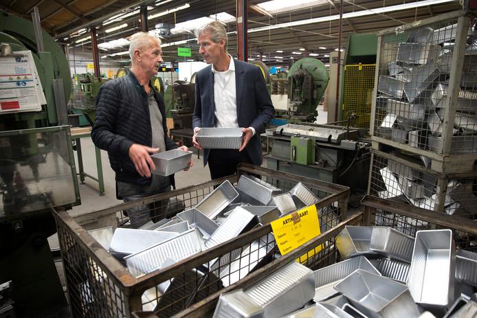 Eigenaar Jan Kaak (rechts) en jubilaris Richard Berentsen bij de machines waar hijtientallen jaren heeft gewerkt.