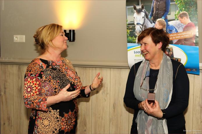 Betsy van de Camp (rechts) neemt de erkenning in ontvangst.
