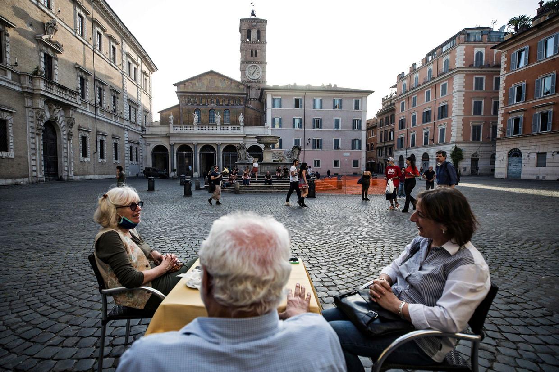 Mensen eten op 18 mei bij een restaurant in Rome, waar de lockdown stap voor stap wordt versoepeld. Beeld EPA