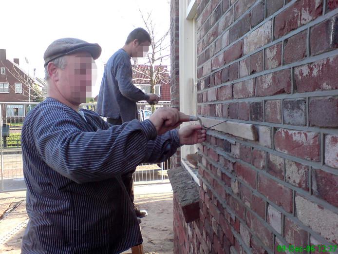 Aannemer Henk K. voegt met een van zijn zonen een muur.